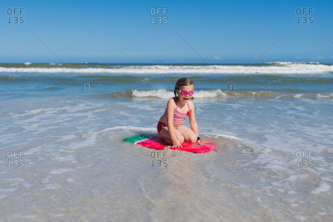 Little girl happily kneeling on body board in shallows at beach