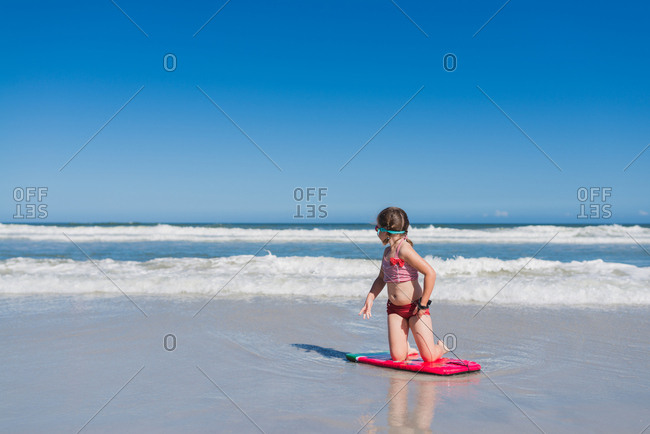 Little girl kneeling on body board and looking around for more waves at the beach