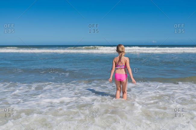 Young girl hesitating as she wades into water at beach