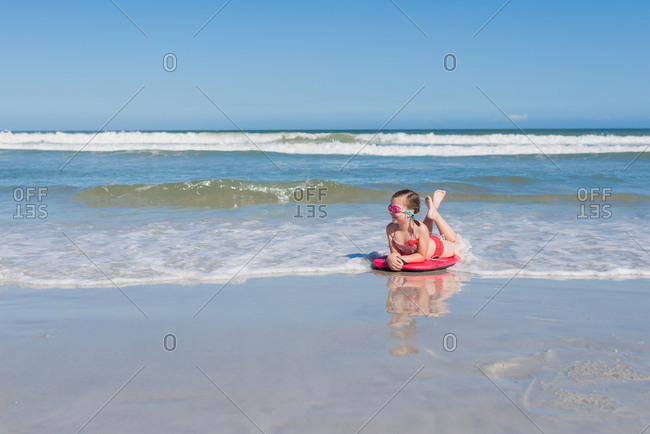 Little girl lying on body board as waves wash over her at beach