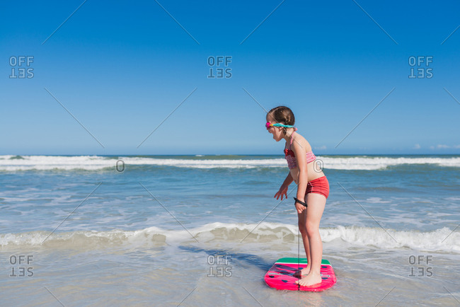 Little girl thrilled that she can stand on body board in water at beach