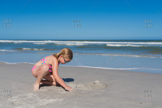 Young girl digging in the sand at waters edge at beach