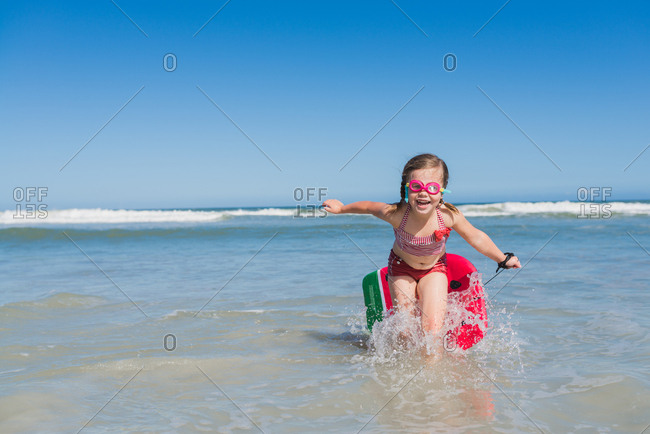 Little girl running out of water dragging body board behind her at the beach