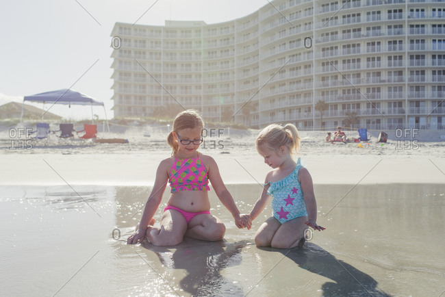 Little girl and sister kneeling in sand holding hands at the beach