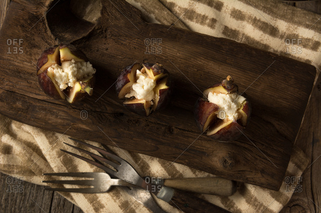 Organic raw figs with goat's cheese in dramatic lighting