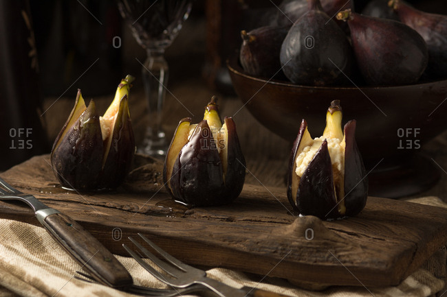 Organic baked figs with goat's cheese and honey in dramatic lighting