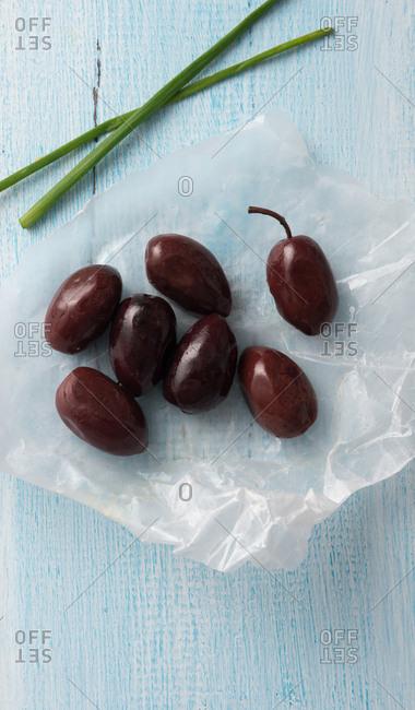 Marinated Greek black olives on wax paper