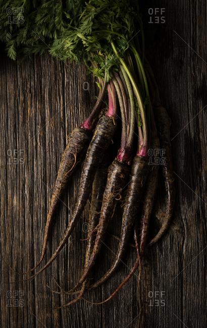 Organic heirloom purple carrots on rustic wood