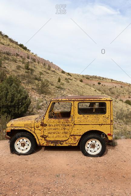 Arizona, USA - March 20, 2014: Old rusty yellow car in a scrap yard