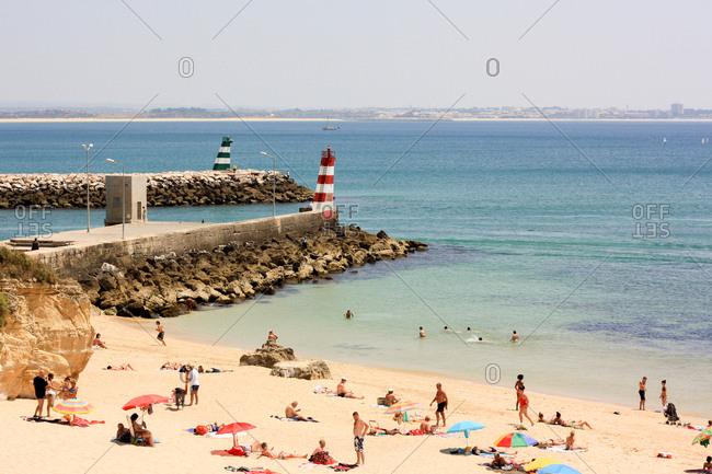 Lagos, Portugal - July 2, 2011: Sunbathers on a sandy beach in Lagos, Portugal