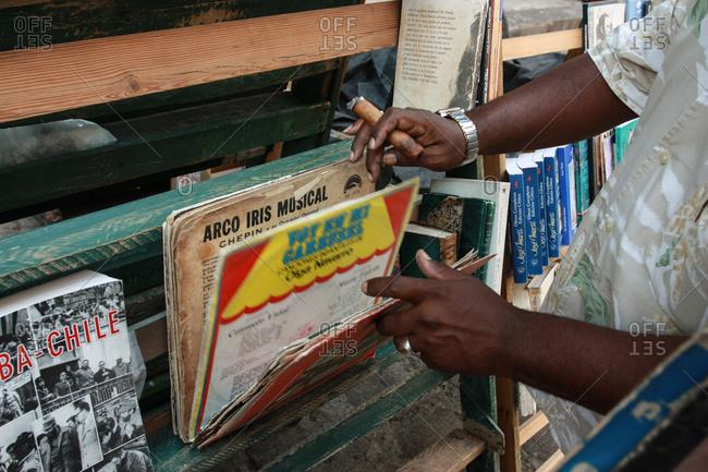 Havana, Cuba - May 25, 2012: A man flips through records holding a cigar in Havana, Cuba