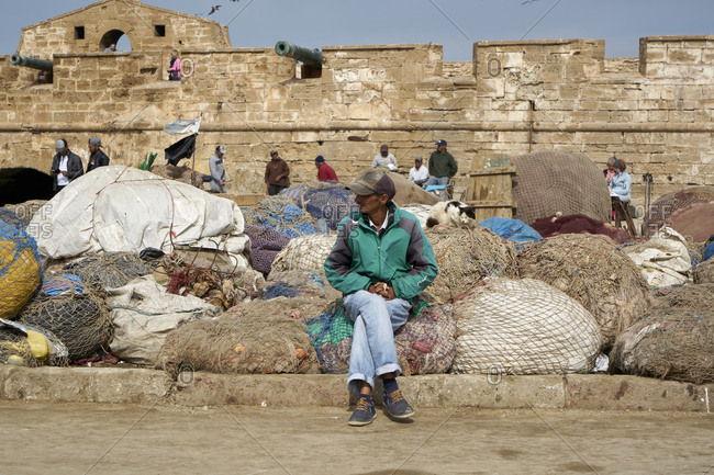 The Port of Essaouira, Essaouira, Morocco; November 8 2017; Man sitting in front of fishing nets at Essaouira Port, formerly Mogador, Morocco, North Africa, Africa. The Port of Essaouira is not only home to many fishing boats and vessels, it is a popular tourist attraction and has a significant and interesting history attached to it. Fishing is done for local distribution and plays a significant role in the atmosphere and lure to the port.