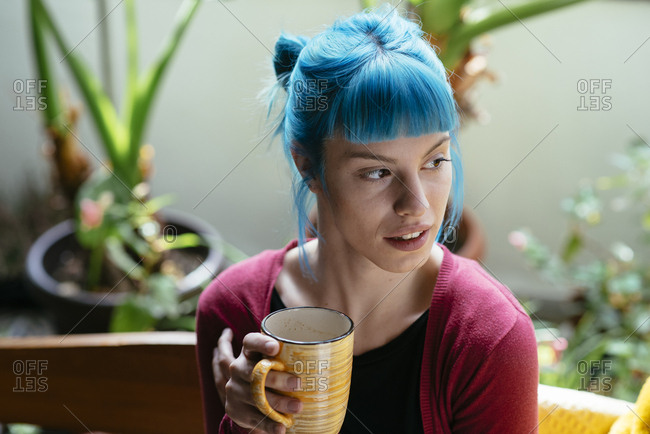 Young hipster woman with stylish blue dyed hair drinking coffee