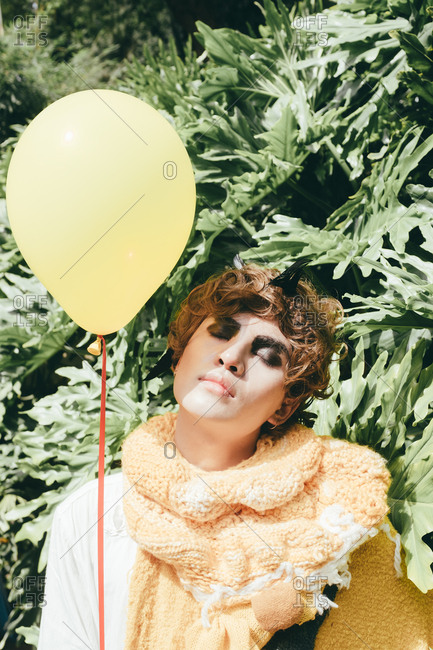 Fashion Asian young man portrait with a yellow balloon