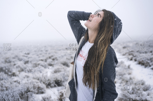 Woman with long hair looking up while standing on snow covered field