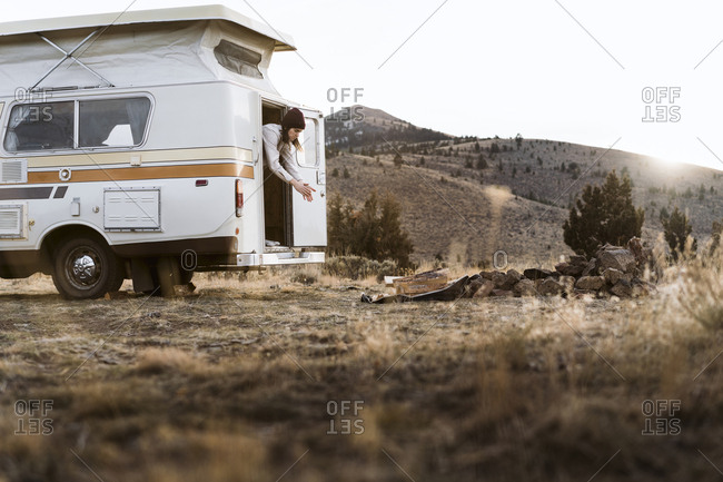 Woman dusting hands while standing in camper van on field against clear sky