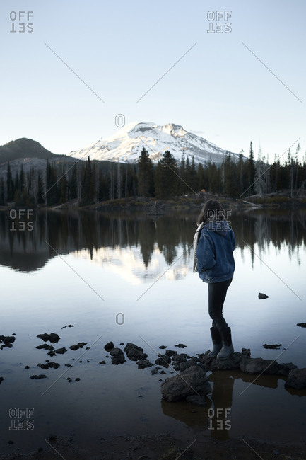 Full length of woman standing on rocks in lake against snowcapped mountain