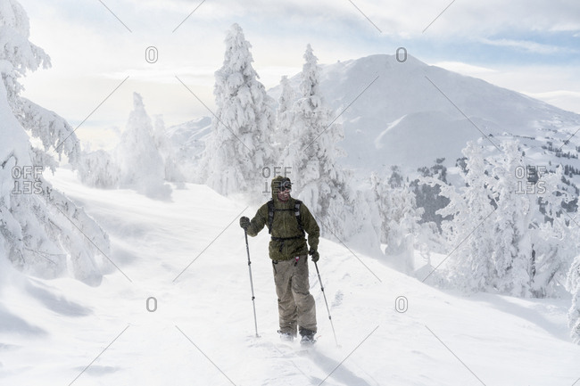 Full length of man with ski equipment standing on snowcapped mountain during foggy weather