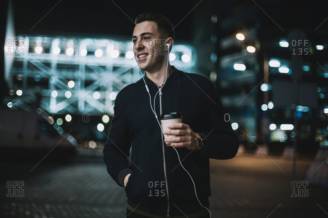 Smiling man with disposable cup listening music while standing against building in city at night