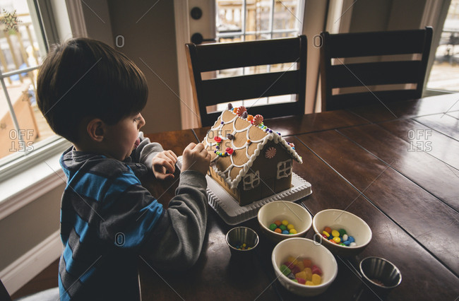 High angle view of boy making gingerbread house on wooden table during Christmas at home