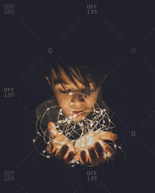Close-up of boy holding illuminated string lights in darkroom
