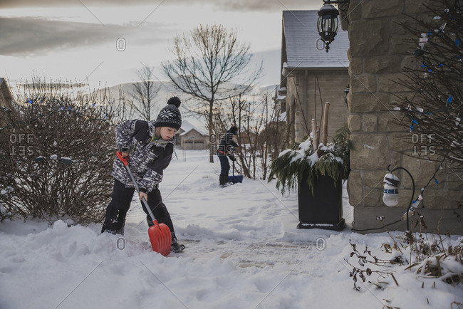 Brothers shoveling snow from backyard