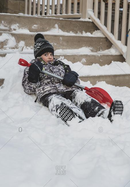 Portrait of boy with shovel lying on snowy steps
