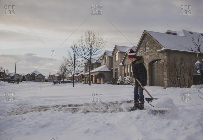 Boy removing snow using shovel against houses