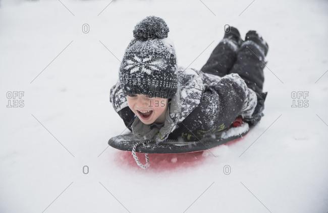 Cheerful boy tobogganing on snow during snowfall