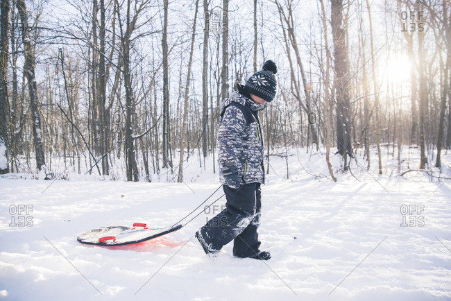 Side view of boy with sled walking on snowy field against bare trees