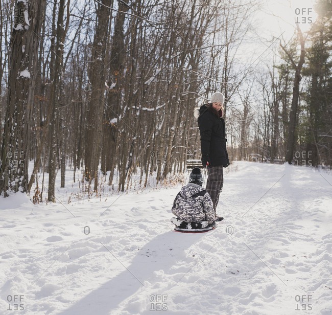 Mother pulling sled with son on snowy field against bare trees