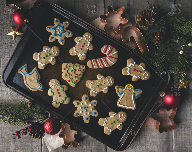 Overhead view of gingerbread cookies in baking sheet by pastry cutters on table