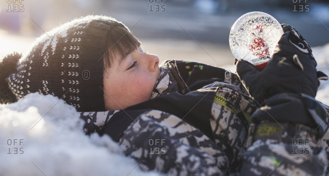 Side view of boy looking at snow globe while lying outdoors during winter
