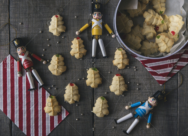 Overhead view of figurines with cookies on wooden table during Christmas
