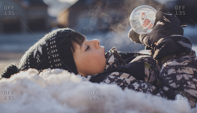 Side view of boy with snow globe lying outdoors during winter