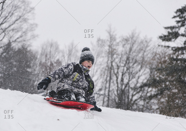 Boy sitting on sled while tobogganing on snow during snowfall