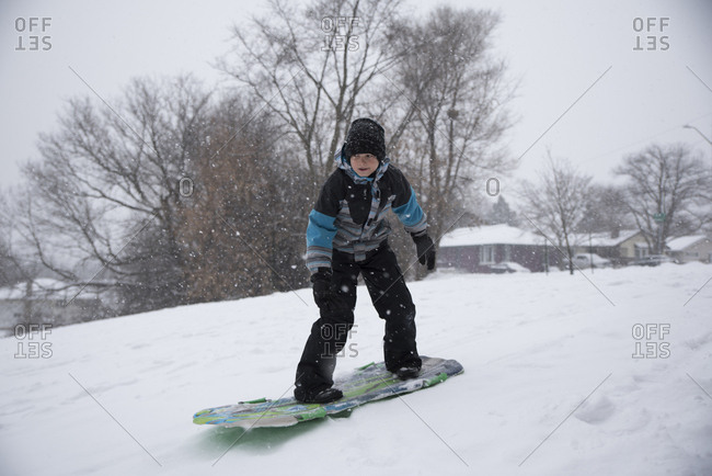 Full length of boy tobogganing on snow during snowfall
