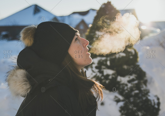Side view of woman exhaling breath vapor during winter