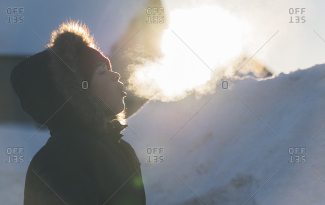Side view of boy wearing fur coat while exhaling breath vapor during winter