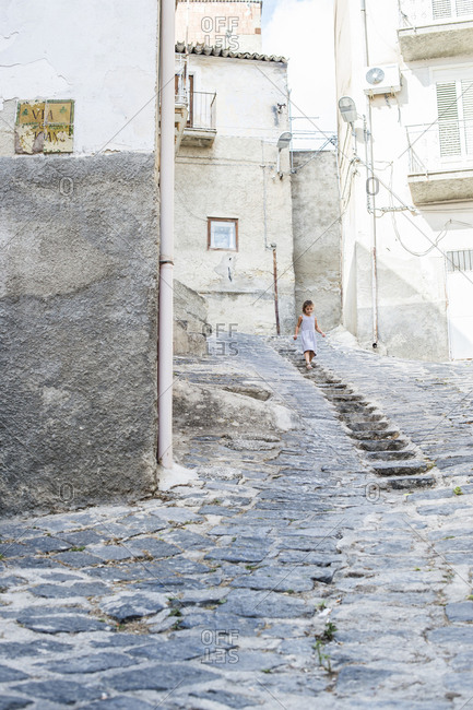 Girl moving down steps amidst on buildings