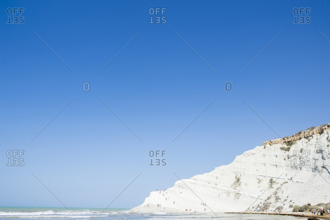 Scenic view of sea by cliff against clear blue sky during sunny day