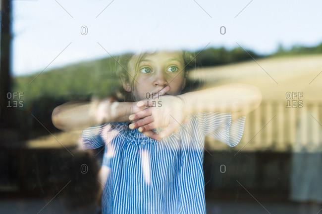 Thoughtful girl looking through window seen through glass