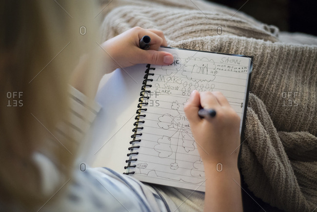High angle view of girl writing in diary while sitting at home