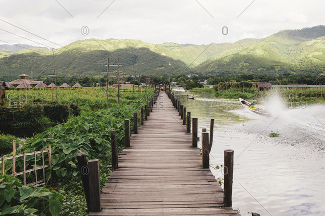 Footbridge over Inle Lake by field against mountains