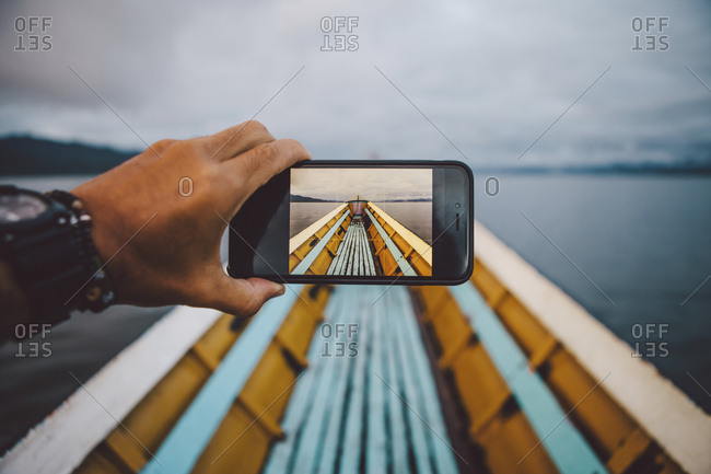 Cropped hand of man photographing boat through smart phone against sky