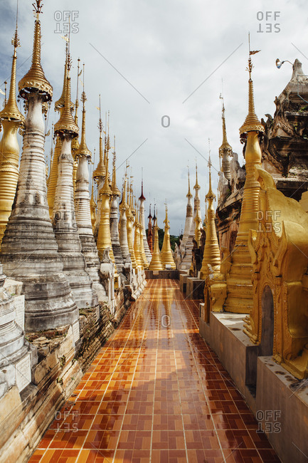 Pathway amidst stupas at Shwe Indein Pagoda against sky