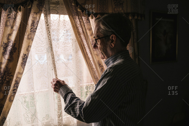 Side view of senior man holding curtain while looking through window in darkroom