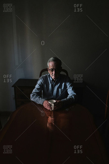 Senior man with coffee cup sitting at table in darkroom