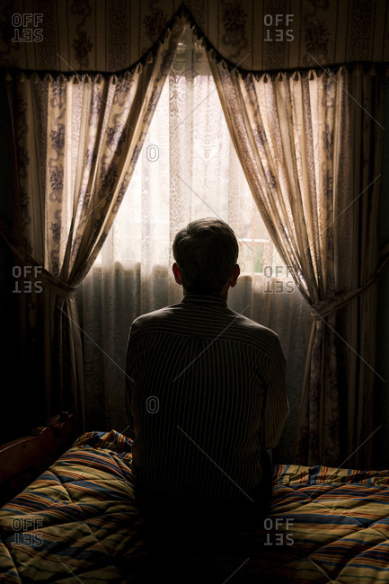 Rear view of senior man sitting on bed against curtains hanging window in darkroom