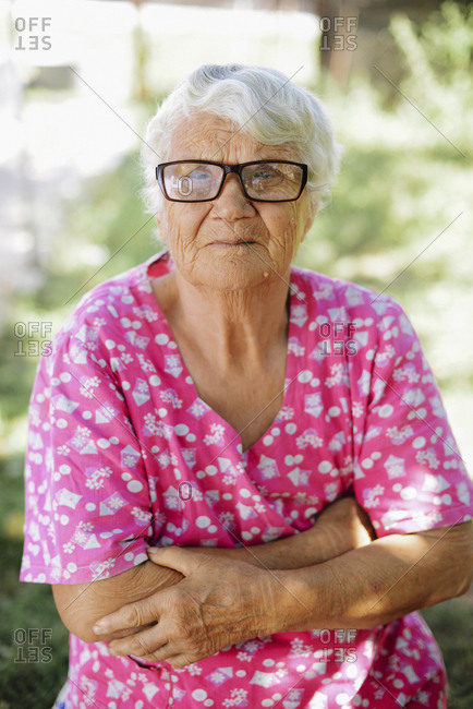 Portrait of senior woman with arms crossed wearing eyeglasses at backyard